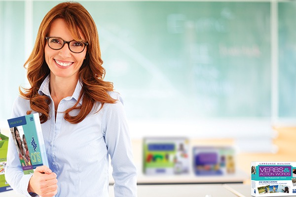 Smiling female teacher in front of blackboard with Stages Learning Materials products