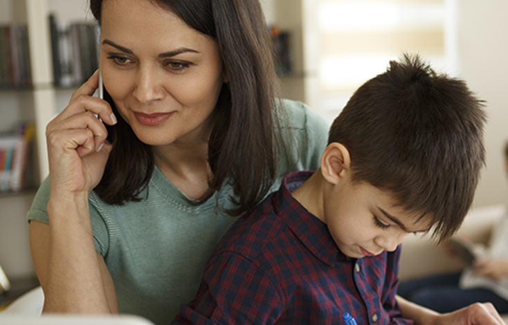 Mom on phone with young boy on lap