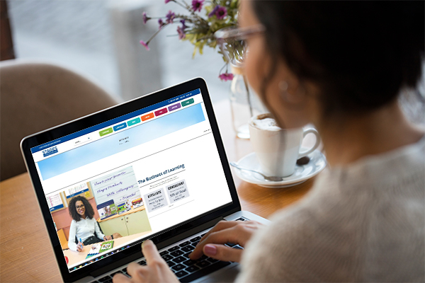 Woman looking at laptop screen with SLC sign up page