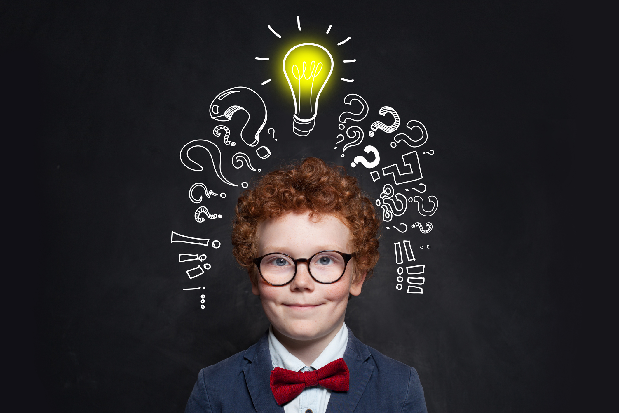 Child and lightbulb on blackboard background