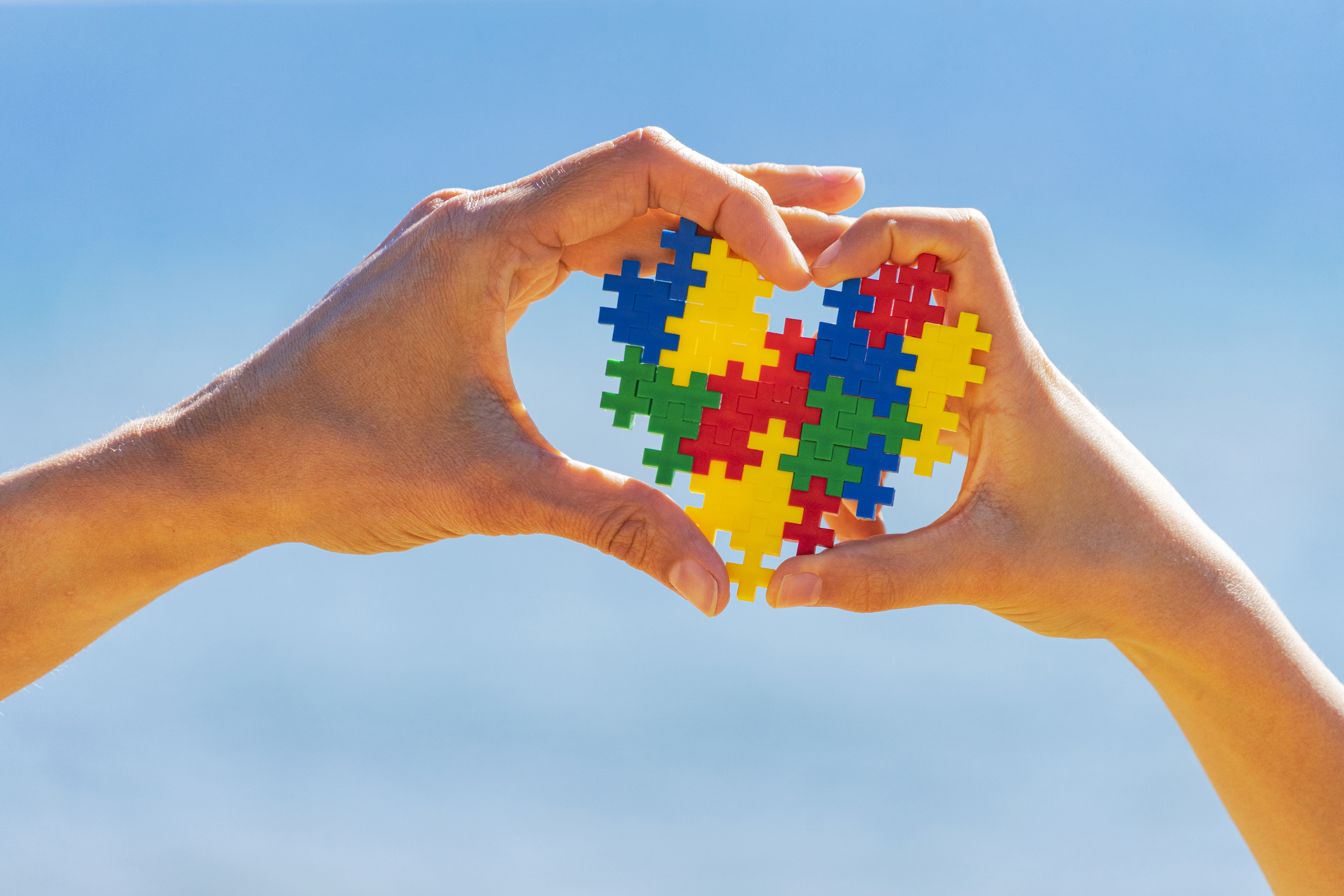 Child and adult hands holding colorful heart on blue sky background. World autism awareness day concept.