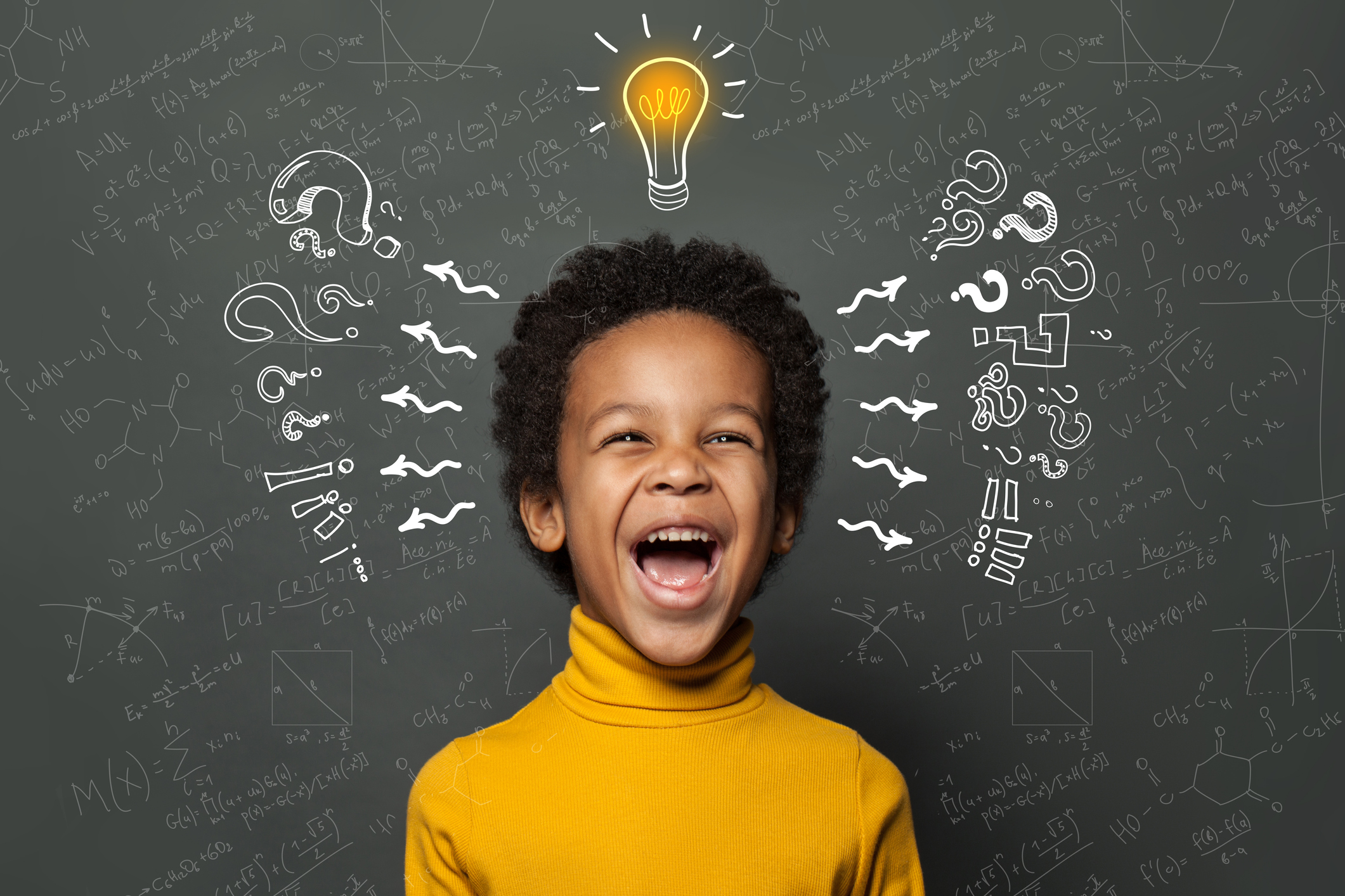 Smart black kid student with lightbulb on blackboard background. Brainstorming and idea concept