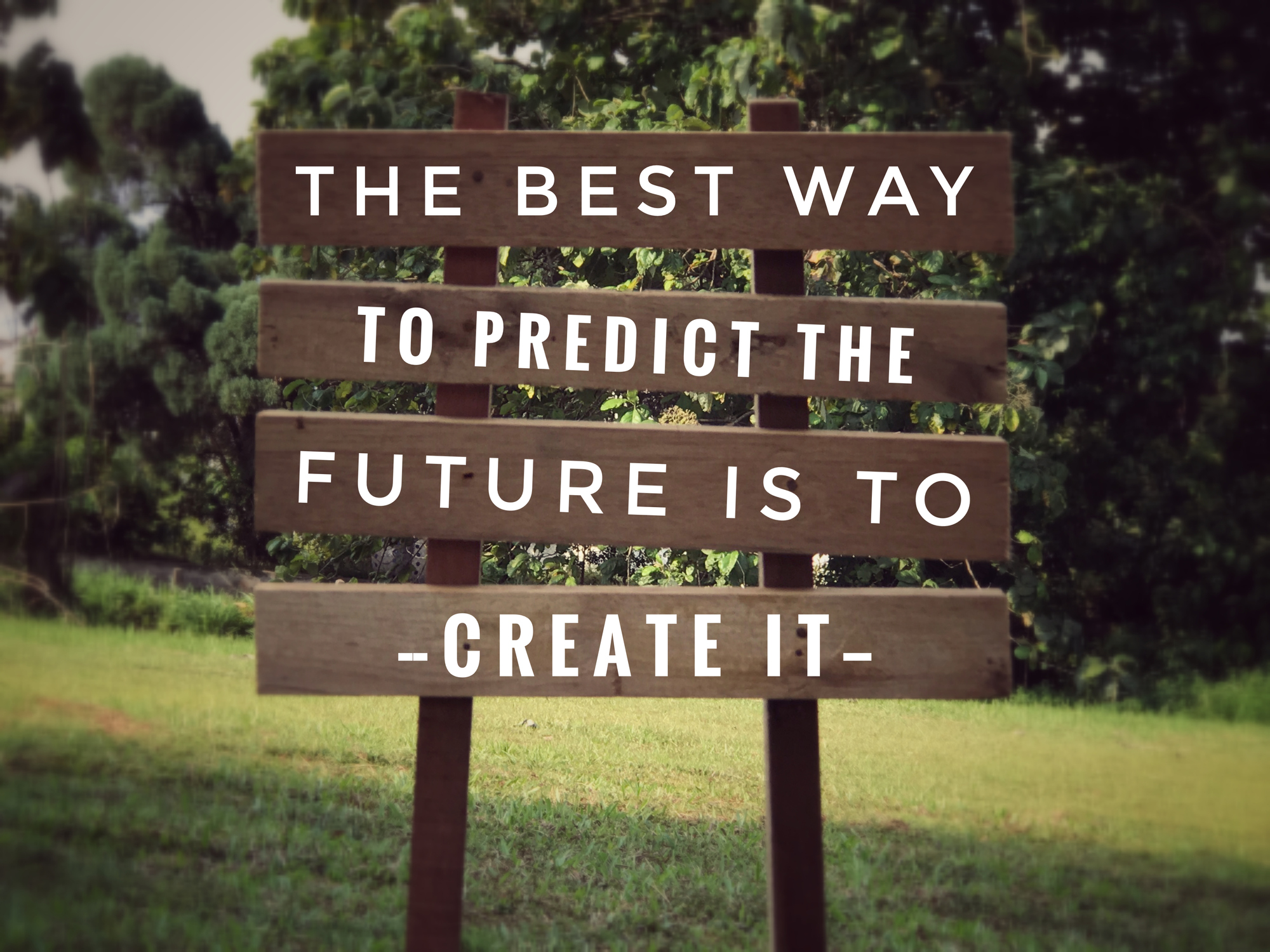 'The best way to predict the future is to create it' on plank signage. With vintage styled background.