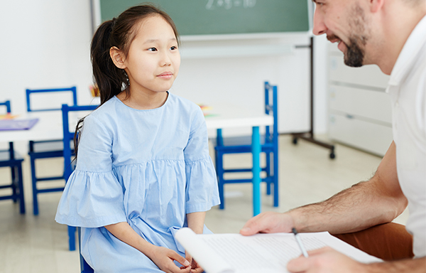 Teacher with clipboard talks to young girl