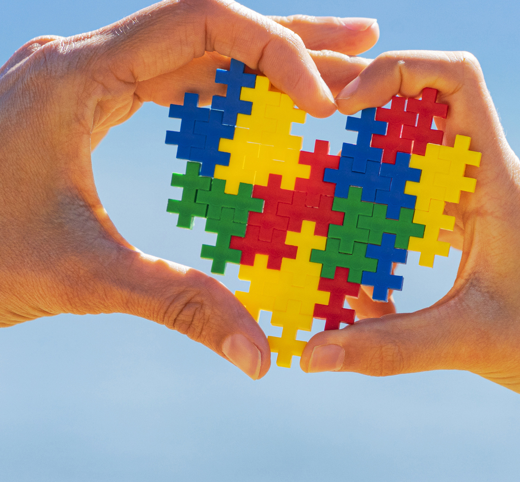 hands holding autism puzzle pieces in shape of heart